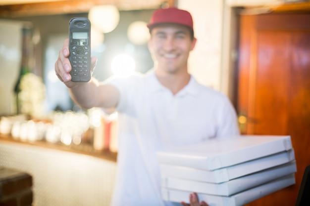 Entregador de pizza, segurando o telefone