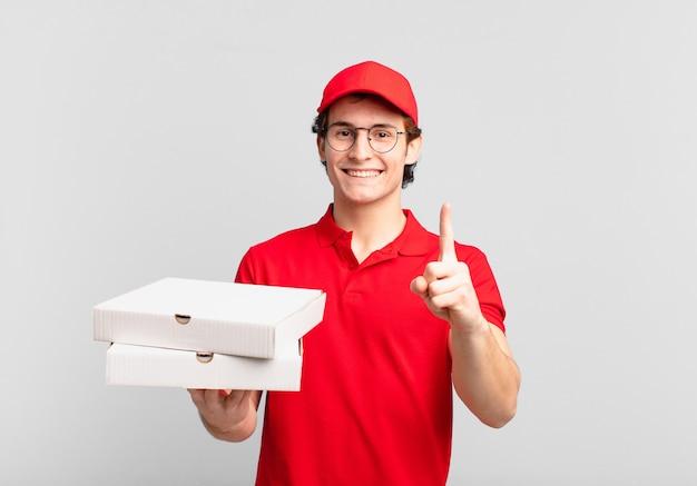 Entregador de pizza sorrindo com orgulho e confiança fazendo a pose número um triunfantemente, sentindo-se um líder