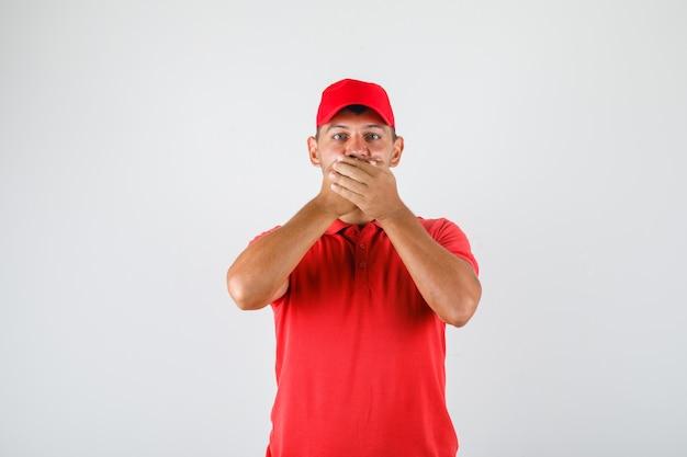 Entregador de uniforme vermelho cobrindo a boca com as mãos por engano e parecendo animado