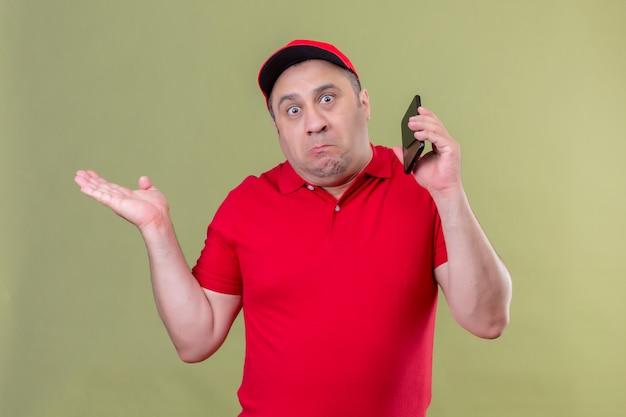 Entregador de uniforme vermelho e boné em pé com smartphone encolhendo os ombros, estendendo as mãos sem entender o que aconteceu expressão confusa e sem noção em pé