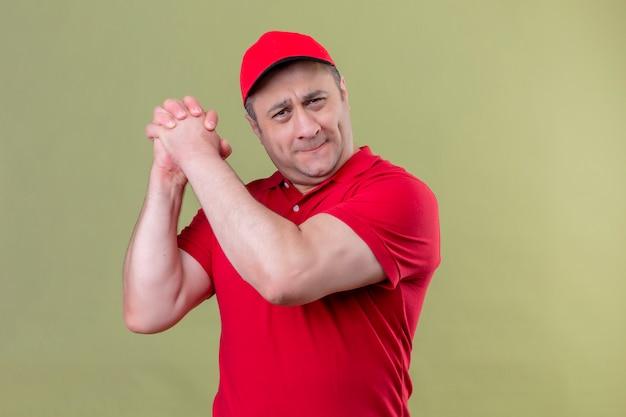 Entregador de uniforme vermelho e boné em pé com um gesto de trabalho em equipe sorrindo confiante no verde isolado