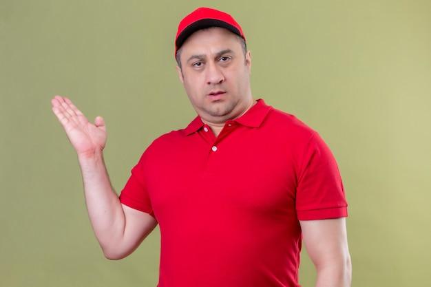 Entregador de uniforme vermelho e boné enquanto se apresenta com a mão com expressão séria no rosto de pé sobre um espaço verde isolado