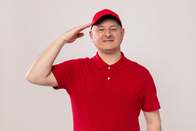 Entregador de uniforme vermelho e boné parecendo sorridente e confiante saudando