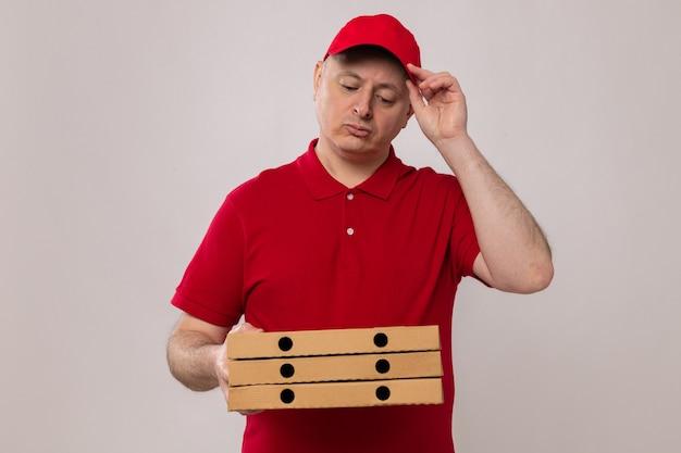 Entregador de uniforme vermelho e boné segurando caixas de pizza olhando para elas perplexo em pé sobre um fundo branco