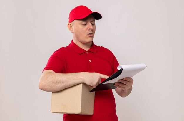 Entregador de uniforme vermelho e boné segurando uma caixa de papelão e uma prancheta olhando para ela com uma cara séria de pé sobre um fundo branco