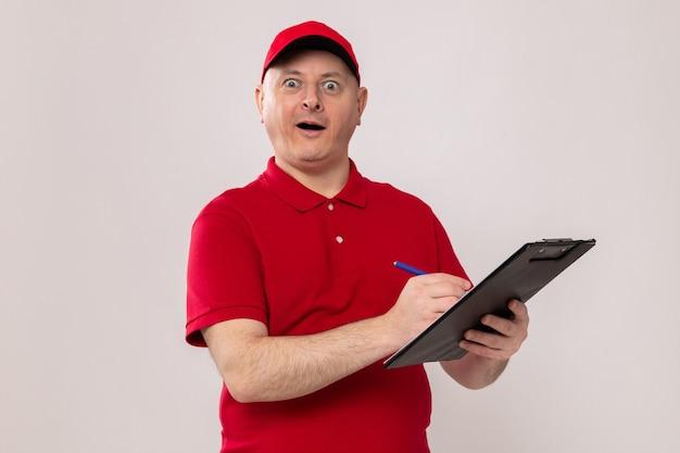 Entregador de uniforme vermelho e boné segurando uma prancheta e uma caneta, fazendo anotações olhando para a câmera feliz e animado em pé sobre um fundo branco