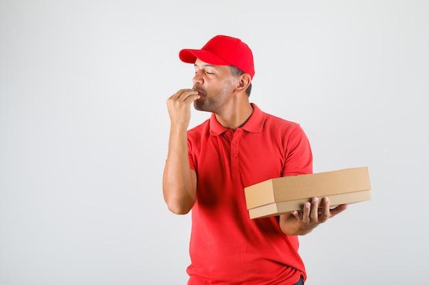 Entregador de uniforme vermelho fazendo gesto saboroso enquanto segura uma caixa de pizza