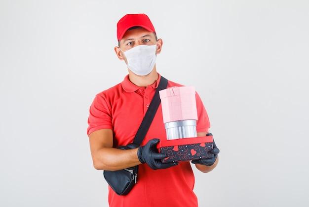 Entregador de uniforme vermelho, máscara médica, luvas segurando caixas de presentes