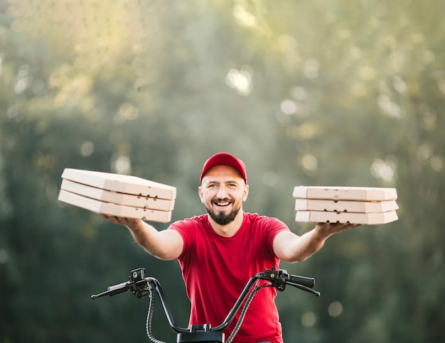 Entregador de vista frontal segurando caixas de pizza