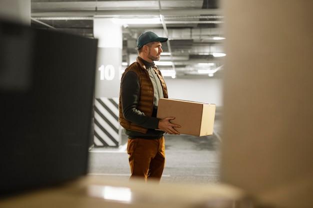 Entregador de vista lateral com pacote