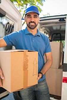 Entregador, descarregando caixas de papelão da van.