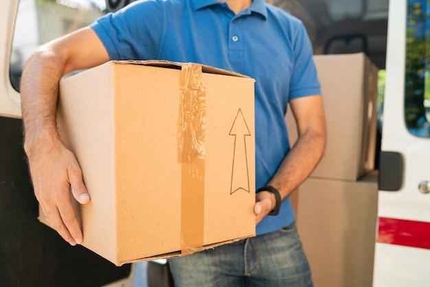 Entregador, descarregando caixas de papelão da van