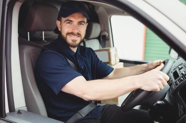Entregador dirigindo sua van enquanto sorrindo para a câmera