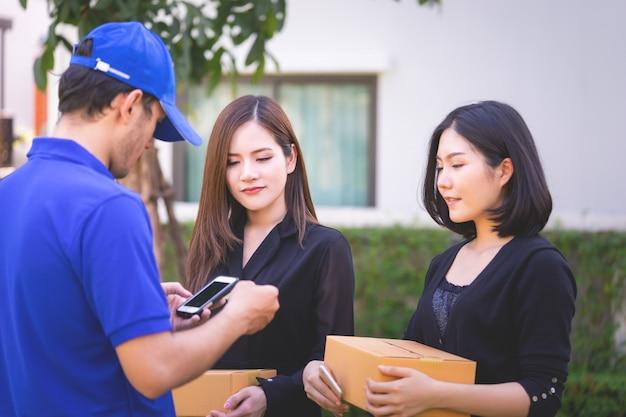 Entregador em azul está entregando pacotes para duas mulheres