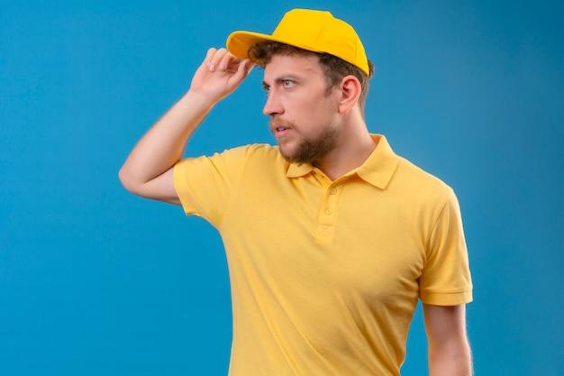 Entregador em camisa pólo amarela e boné olhando para o lado fazendo gesto de saudação tocando seu boné no azul isolado