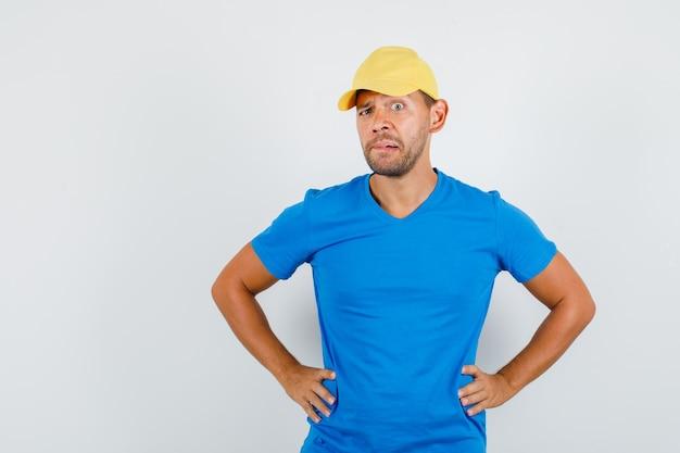 Entregador em pé com as mãos na cintura em camiseta azul