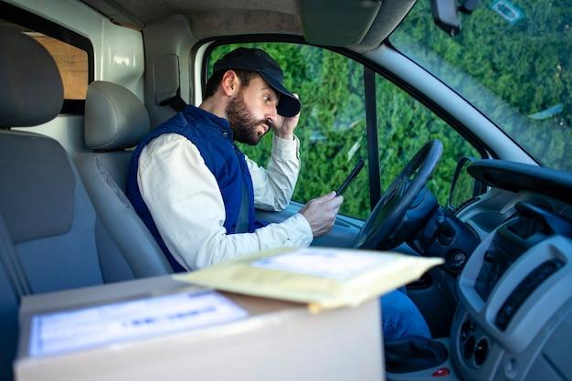 Entregador em sua van com dificuldade em encontrar o endereço apropriado para entregar o pacote.
