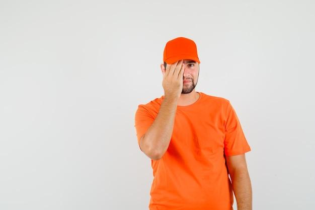 Entregador em t-shirt laranja, boné cobrindo os olhos com a mão e olhando positiva, vista frontal.