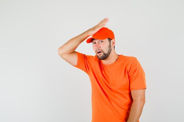Entregador em t-shirt laranja, boné segurando a palma da mão na cabeça e olhando desculpe, vista frontal.