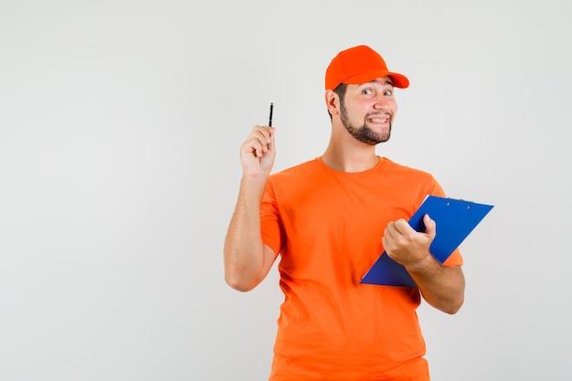 Entregador em t-shirt laranja, boné segurando a prancheta e caneta e olhando alegre, vista frontal.
