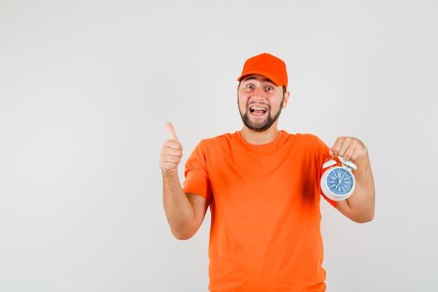 Entregador em t-shirt laranja, boné segurando o relógio despertador com o polegar para cima e olhando feliz, vista frontal.