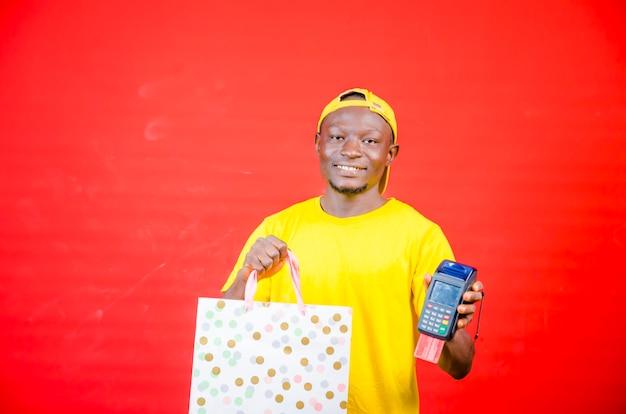 Entregador em traje de trabalho amarelo segura terminal de pagamento do banco para processar pagamentos de aquisição com cartão de crédito