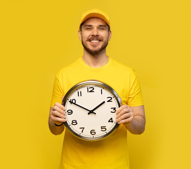 Entregador em trajes de trabalho amarelos segurar o relógio isolado no retrato de estúdio de fundo amarelo.
