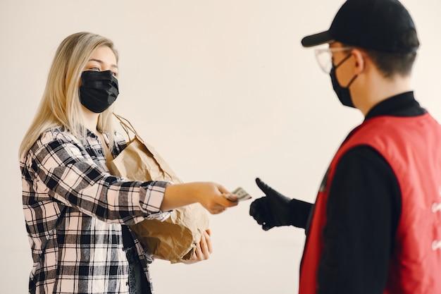 Entregador em uma máscara de médico com mulher