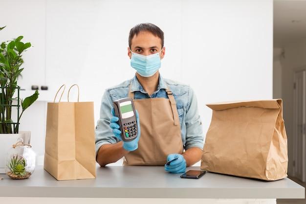 Entregador em uma máscara protetora e luvas mantém o terminal pos na mão. conceito de vírus coronavírus pandêmico de quarentena de serviço