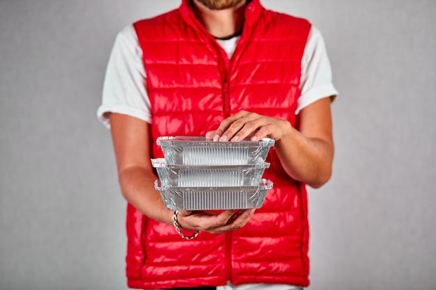 Entregador em uniforme de colete vermelho segurar o serviço de entrega de comida ir caixa isolado. entrega de comida em restaurantes para viagem em casa