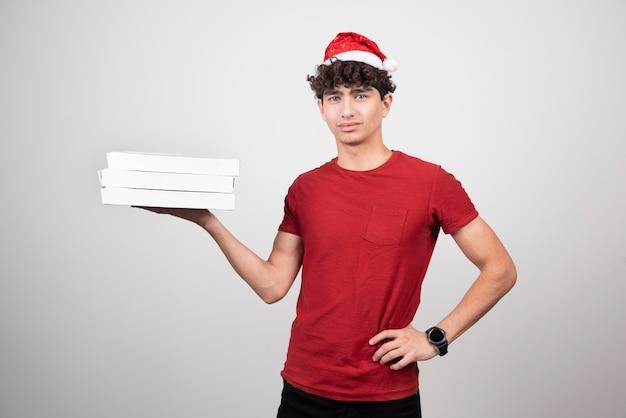 Entregador encaracolado com chapéu de papai noel segurando caixas de pizza.