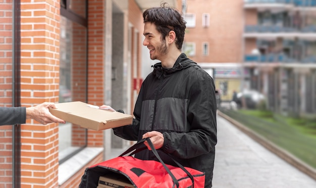 Entregador entregando comida para o cliente em casa, segurando uma sacola vermelha