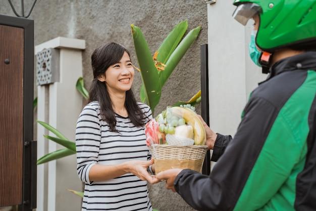 Entregador, entregando frutas parcela