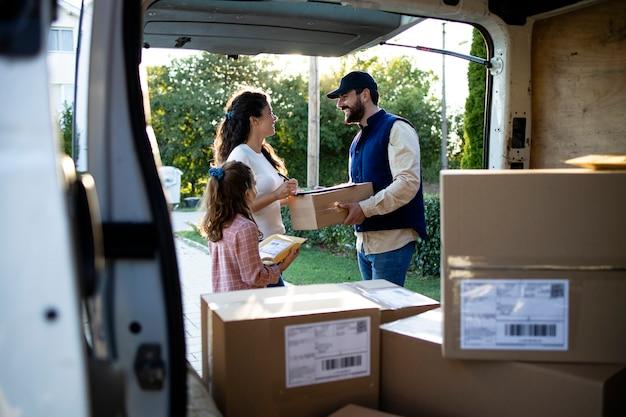 Entregador entregando pacotes aos clientes na frente da casa.