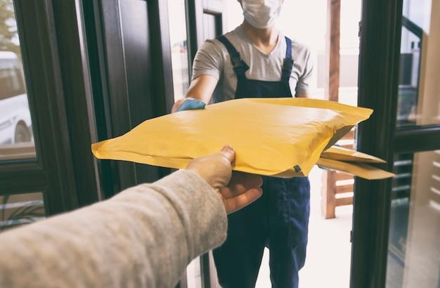 Entregador entregando pacotes para o cliente em casa