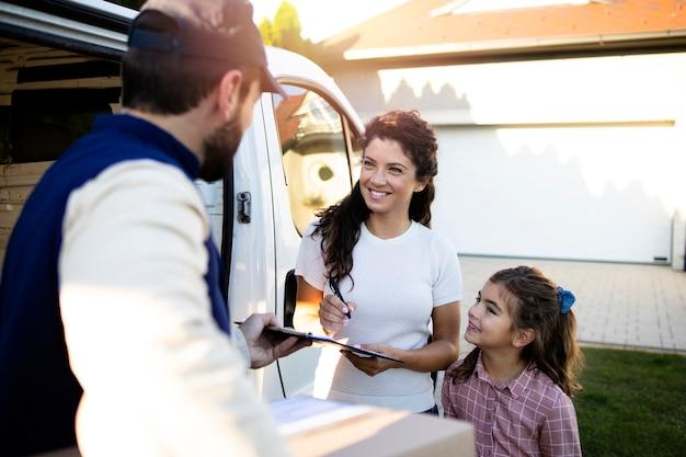 Entregador entregando pacotes para uma linda mulher e a filha dela na frente da casa.