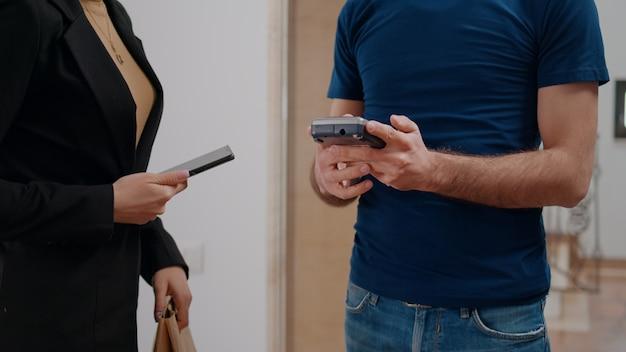 Entregador entregando um pedido de comida para uma mulher de negócios no escritório da empresa startup durante a hora do almoço