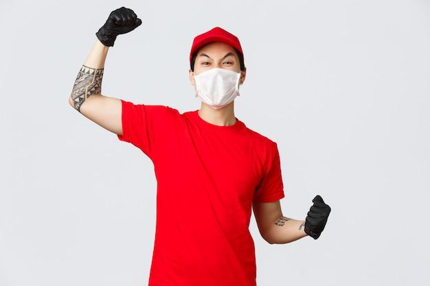 Entregador entusiasmado alegre de camiseta vermelha e boné, usando máscara médica, luvas protetoras, levantando a mão para cantar, diga sim ou viva, comemore o sucesso, incentive o pedido on-line
