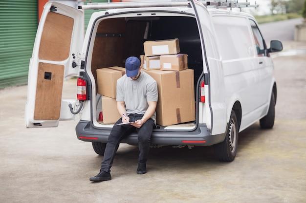 Entregador, escrevendo na área de transferência enquanto está sentado na área de carga de sua van
