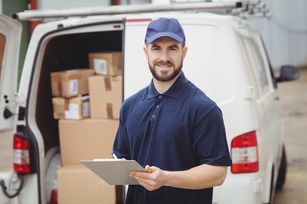 Entregador, escrevendo na área de transferência na frente de sua van