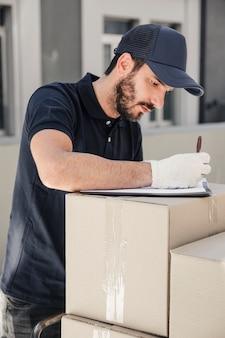 Entregador, escrevendo na área de transferência sobre caixas de papelão empilhadas