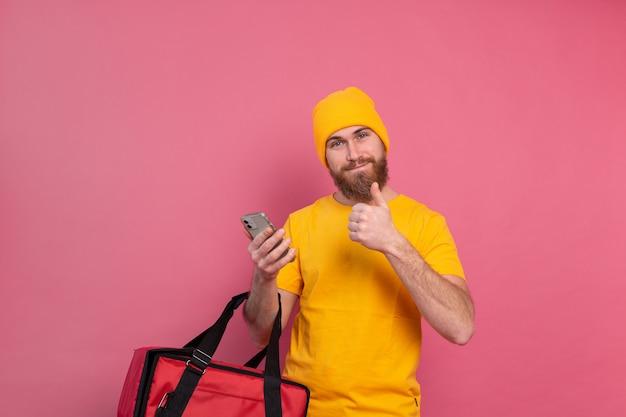 Entregador europeu alegre com bolsa casual segurar telefone rosa