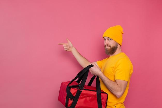 Entregador europeu barbudo com caixa com comida sorrindo e apontando o dedo para a esquerda na rosa