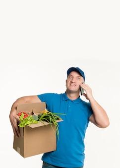 Entregador, falando no telefone e segurando a caixa de supermercado
