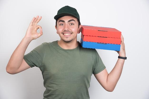 Entregador fazendo sinal de ok e segurando caixas de pizza em fundo branco.