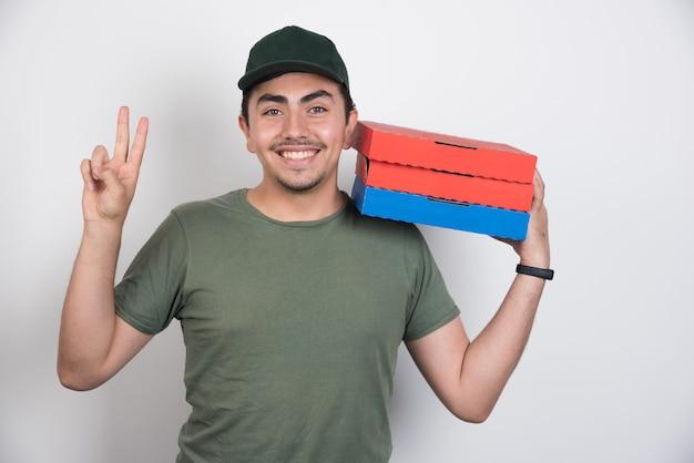 Entregador, fazendo sinal e segurando três caixas de pizza no fundo branco.