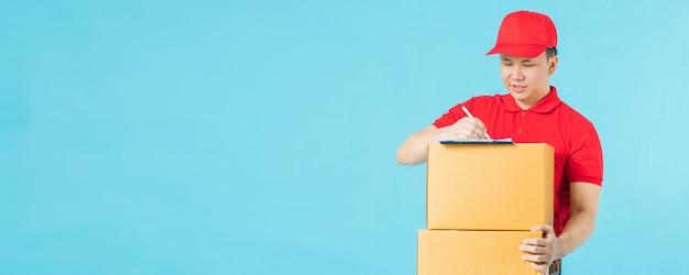 Entregador feliz asiático, vestindo uma camisa vermelha, escrevendo o bloco de notas, mantendo caixas de encomendas de papel