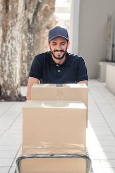 Entregador feliz com caixas de papelão