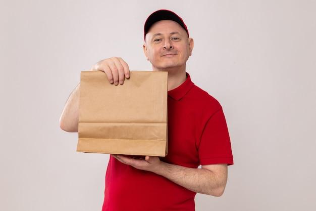 Entregador feliz e positivo de uniforme vermelho e boné segurando um pacote de papel olhando para a câmera sorrindo alegremente em pé sobre um fundo branco
