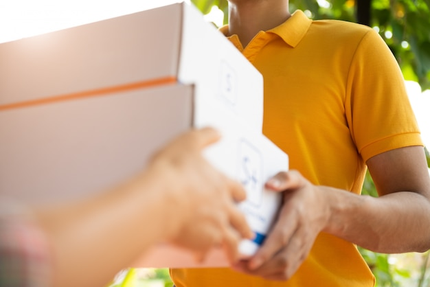 Entregador feliz em camisa polo amarela uniforme com caixa de correio de encomendas nas mãos